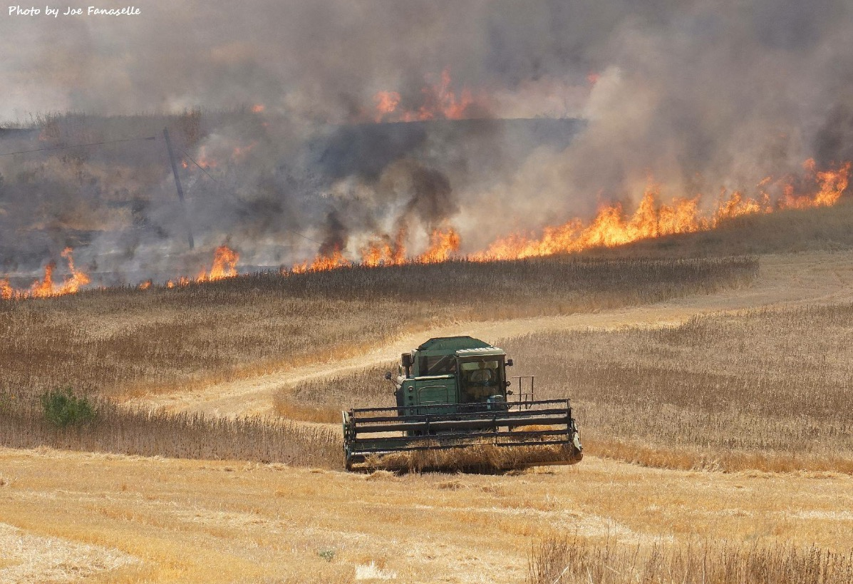 Tractor plowing a field with brush fire in background